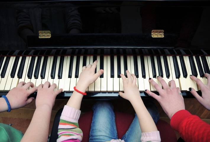 three pairs of hands playing a piano