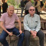 two elderly gentlemen sitting on a bench drinking wine